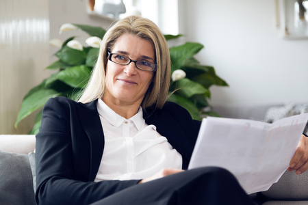 Portrait of attractive middle-aged business woman sitting on modern sofa at home and smiling into the camera. Confident woman with black suit reading white papers in bright living room.