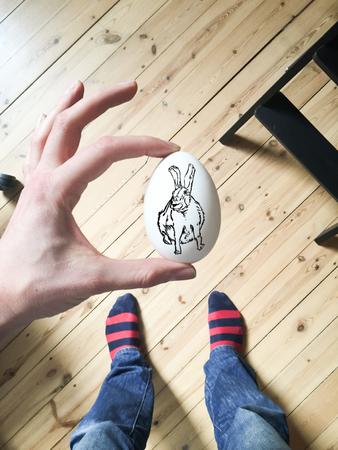 Rabbit sketch on white egg. Hand holding up egg. Hardwood floor in background. Overheads shot.