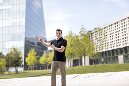 A man making demonstrative hand gestures while standing in front of modern glass building. Reklamní fotografie