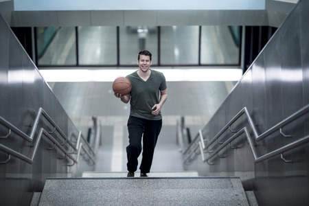A man walking up a stairwell with a basketball in hand. High angle shot.