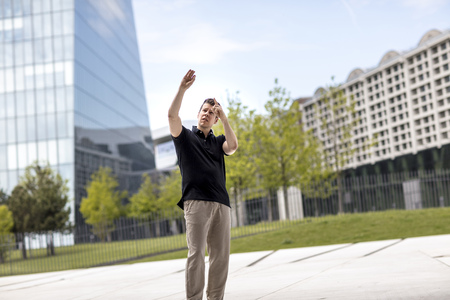 A man making hand gestures while standing in front of modern glass building. Фото со стока