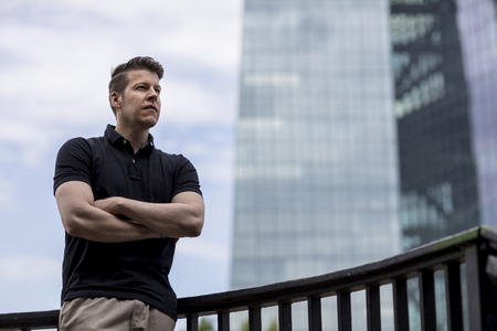 A man standing with his arms crossed and a skyscraper building in the background.