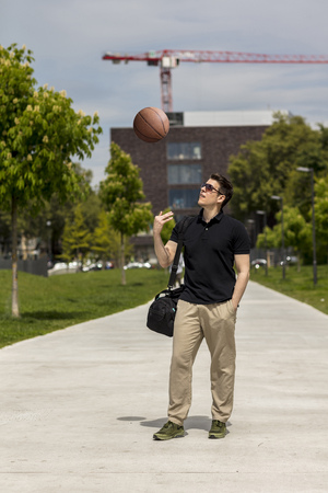 Long shot of a casually dressed man holding a basketball outdoors in an urban park area.