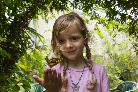 Girl with a  butterfly resting on her fingertips. Low angle view. Medium close-up.