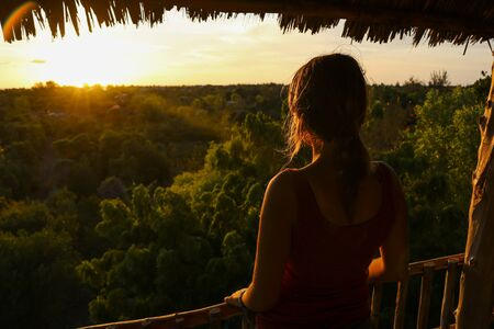 close-up of a woman looking at sunset from tree house