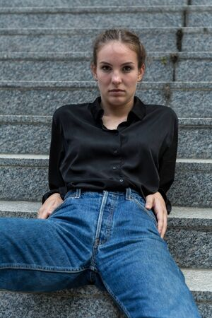 Young Woman Seated Leisurely on Outdoor Steps Looking at Camera