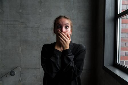 Young Woman with Shocked Facial Expression Covering Mouth with Hands