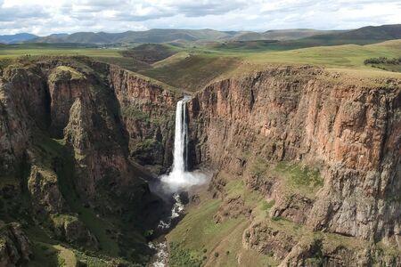horizontal shot of stunning waterfall running down a steap canyon