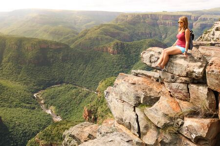 female hiking tourist sitting on mountains and enjoying the view Stock Photo