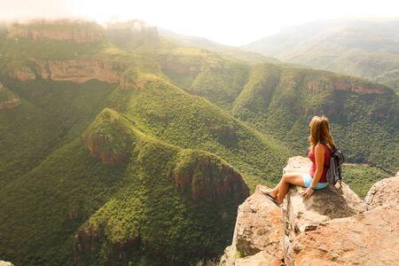 female hiking tourist sitting on mountains and enjoying the view Stockfoto