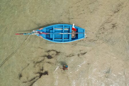 top view drone shot of couple next to a blue sailing boat