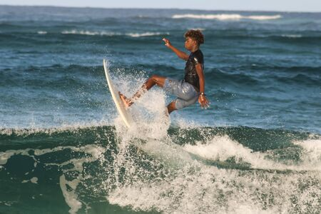 native black african surfer catching a wave in Tofo, Mozambique
