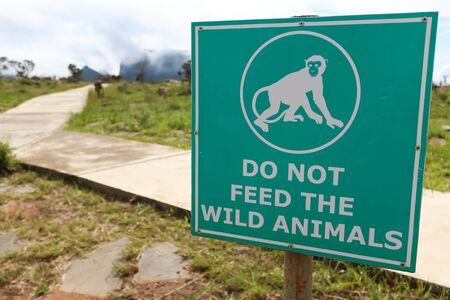 green sign telling to not feed wild animals