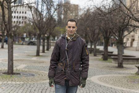Young Man with Earphones Walking in Urban Setting