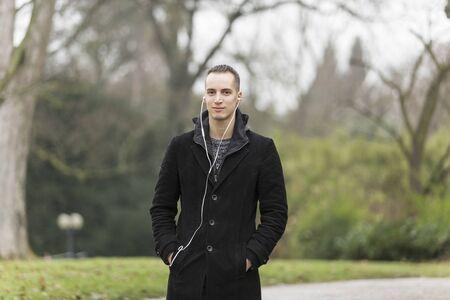 Young Caucasian Man Listening to Earphones and Wearing Black Coat Outdoors Banco de Imagens