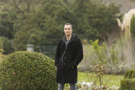 Young Man Listening to Earphones Posing in Topiary Garden