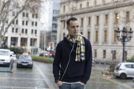 Young Man with Earphones and Head Turned in Urban Setting