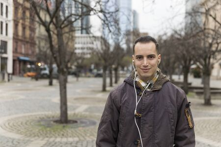 Portrait of Young Man with Earphones on City Street Stockfoto