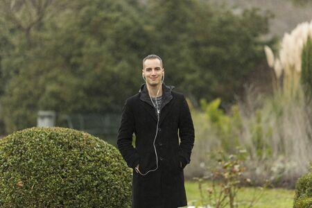 Young Man Wearing Coat and Listening to Earphones Posing in Garden
