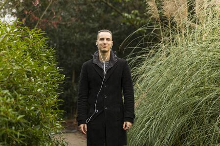 Young Man Posing in Garden Wearing Coat and Listening to Headphones