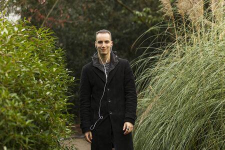 Young Man with Earphones and Coat Standing in Botanical Garden