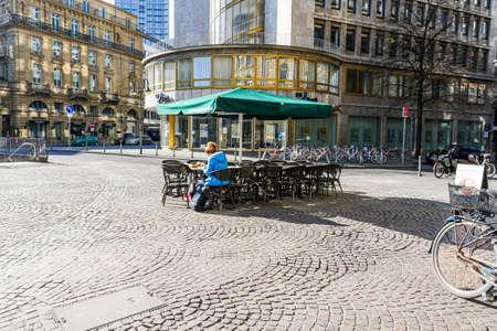 Coronavirus lockdown. Frankfurt, Germany. April 5, 2020. Single customer sitting at coffee shop table outdoors during covid-19 crisis. Editorial
