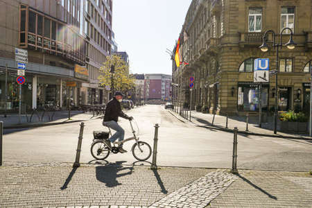 Coronavirus lockdown. Frankfurt, Germany. April 5, 2020. Old man riding bicycle on empty street wearing a mask. Profile view.