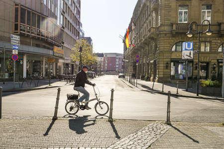 Coronavirus lockdown. Frankfurt, Germany. April 5, 2020. Old man riding bicycle on empty street wearing a mask. Profile view.