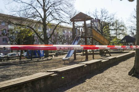 Children's playground with barricade tape preventing access during covid-19 quarantine. Focus on foreground.
