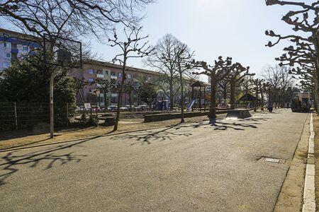 Neighborhood park with children's play area in Frankfurt with few people. Coronavirus quarantine. Long shot.