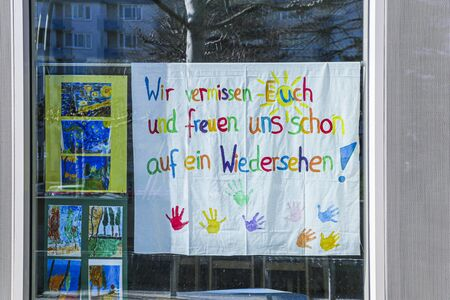 We miss you and hope to see you soon children's sign with handprints written in German. Banco de Imagens