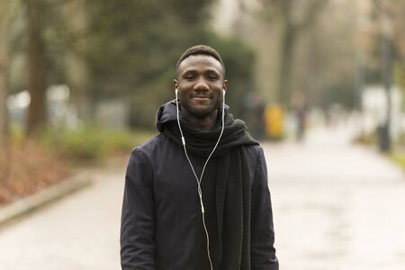 Young Man Listening to Earphones Smiling Confidently at Camera