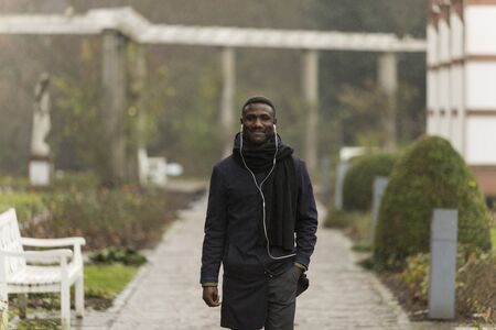 Confident Young Black Man Walking in Park