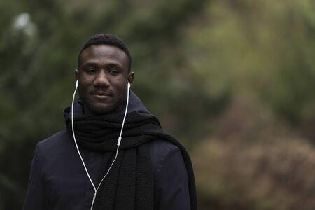 Portrait of Young Black Man Listening to Earphones in Park Banco de Imagens