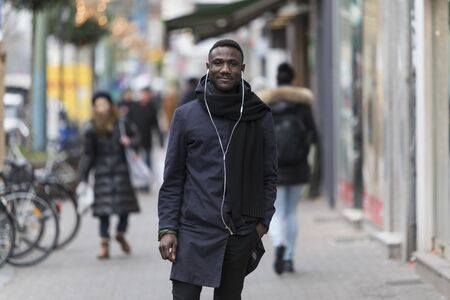 Portrait of Black Man with Earphones and Coat Posing on Sidewalk Stockfoto