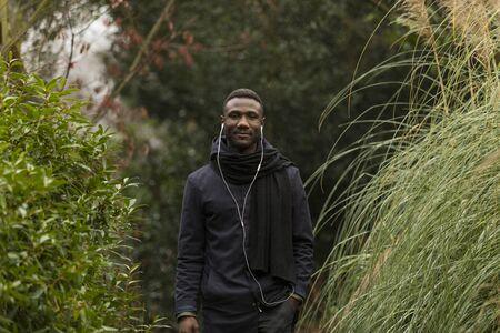 Young Man with Earphones Posing in Park Banco de Imagens