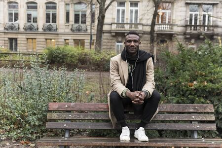 Young Black Man Sitting on Public Park Bench Backrest Banco de Imagens