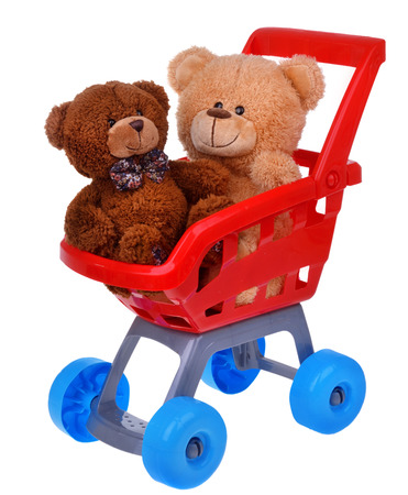 Shopping supermarket cart with teddy bear toys isolated on white photo