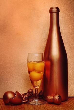 bronze background: Eggs in glass with bronze bottle over grunge bronze background