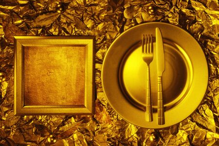 Stll life with plate, fork and knife on gold background photo