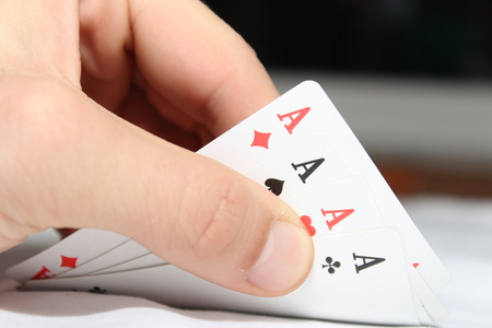 hand holding playing card: Four Poker card of ace in hand Stock Photo