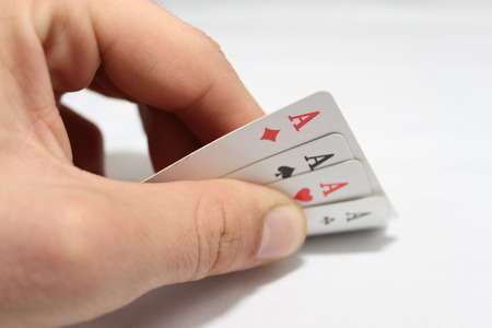 focuses: Closeup photos that focuses on four card of ace in handin poker game on white background