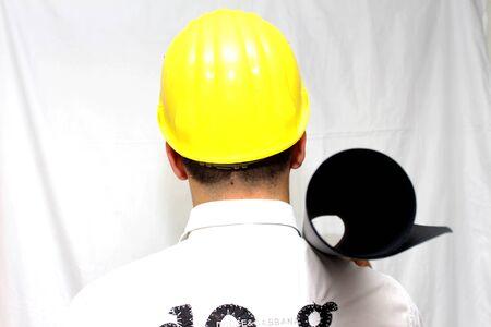 waist shot: Smiling construction worker in yellow helmet. Waist up studio shot isolated on white.