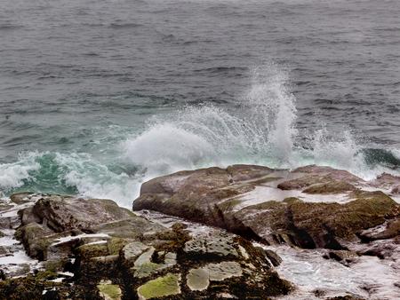 Ocean waves splash against rocks in Beavertail on a cloudy day