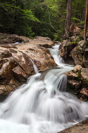 River flows down rocky bed  creating Waterfall flowing over rocks in The Basin New Hampshire on a summer day Stockfoto