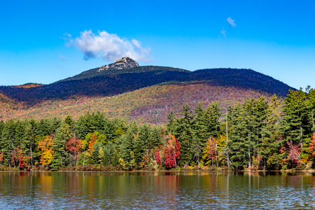 Fall foliage on New Hampshire pond with mountain in the background