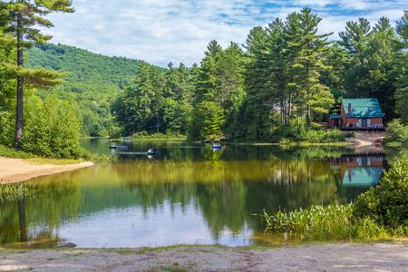 カヤック、水泳できる山を背景に風光明媚な池 写真素材