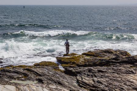 Fisherman on the rocky shore catching fish in Jamestown Beavertail