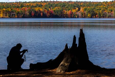 silhouetted of  a man taking pictures with a dslr on a lake Stockfoto