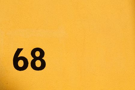 65 69 years: Yellow Facade background, street number 68 Stock Photo